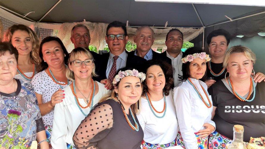 Zdjęcie przedstawia gości Święta Gminy Głowno z powiatu zgierskiego w otoczeniu pań z  Koła Gospodyń Wiejskich.